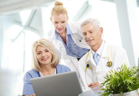 Photo pour Portrait d'une équipe médicale assise au bureau devant un ordinateur et consultant. Groupe médical . - image libre de droit