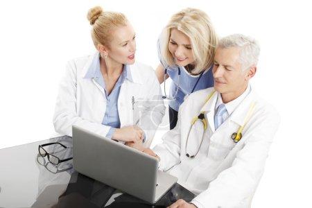 Photo pour Portrait de l'équipe médicale assise devant l'ordinateur et le conseil. Isolé sur fond blanc . - image libre de droit