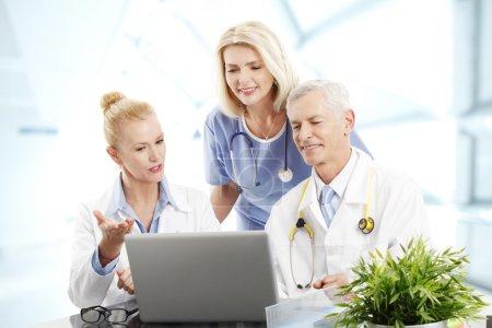 Photo pour Portrait de l'équipe médicale de soins de santé assis devant l'ordinateur tout en consultant. Médecin féminin et médecin masculin assis au bureau tandis que l'assistant médical debout à l'arrière-plan . - image libre de droit