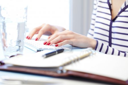 Photo for Young woman fingers with red nails typing on white keyboard, close up - Royalty Free Image