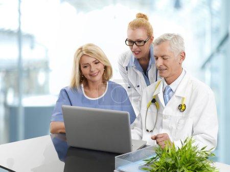 Photo pour Portrait de l'équipe médicale travaillant à l'ordinateur portable et de consultation. Médecins et assistant médical assis devant l'ordinateur et vérifiant le résultat du test médical à la clinique privée . - image libre de droit