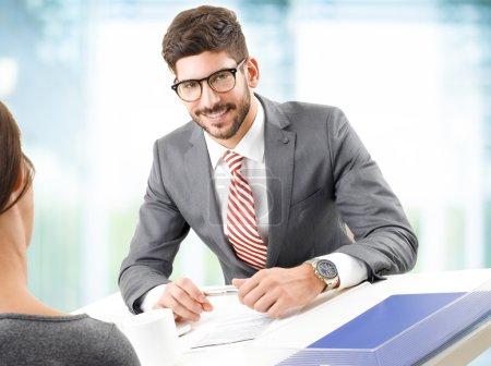 Photo pour Image d'un jeune homme d'affaires assis au bureau devant un ordinateur et faisant un entretien d'embauche avec une employée. Jeune homme d'affaires souriant et regardant la caméra . - image libre de droit