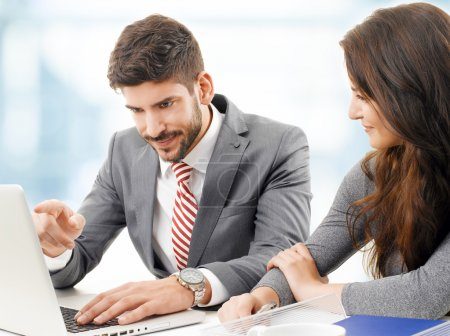 Photo for Portrait of young businesswoman and businessman sitting at desk in front of laptop and working on new project. Teamwork at office - Royalty Free Image