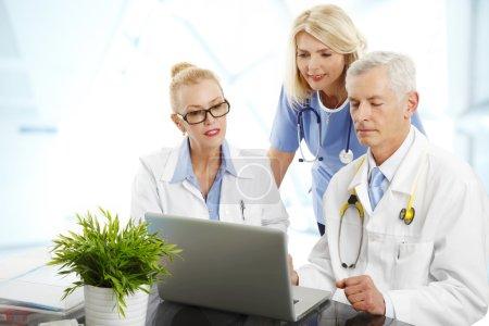Photo pour Portrait du personnel médical assis à l'hôpital. Médecins et infirmières assis devant un ordinateur portable et consultant . - image libre de droit