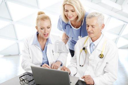 Photo pour Portrait d'une équipe médicale assise devant un ordinateur portable et consultant. Médecins et infirmières analysant les tests médicaux . - image libre de droit