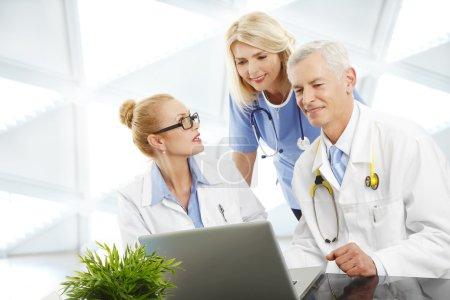 Photo pour Image d'un médecin féminin et d'un médecin consultant une infirmière assis à l'hôpital devant un ordinateur portable . - image libre de droit