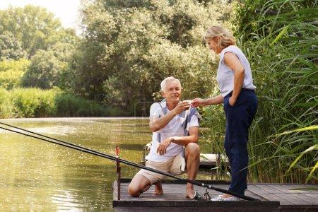 Photo pour Portrait d'un couple de personnes âgées finshing à la jetée. Vieil homme accroupi sur la jetée et montre à sa femme combien de poissons capturés. Ils se détendent au bord du lac . - image libre de droit