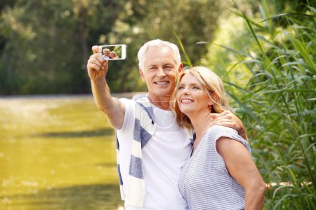 Photo for Portrait of happy senior people standing at lakeside while elderly man taking self portrait with his mobile phone. - Royalty Free Image
