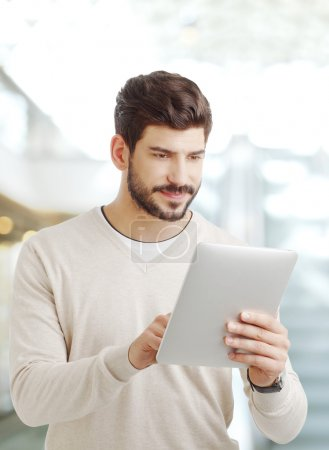 Photo for Portrait of creative man working online. Young businessman standing at office and holding hands digital tablet while touching the screen. - Royalty Free Image