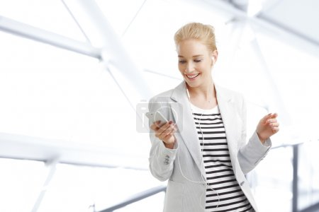 Photo for Portrait of young businesswoman with earphone standing at office and holding hand mobile phone while listening music. - Royalty Free Image