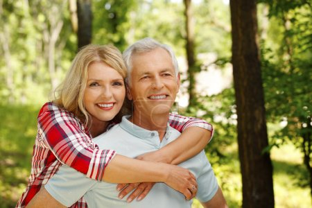 Photo for Portrait of senior couple hiking in the forest. Elderly woman embracing her senior man while standing outdoors and spending time together. - Royalty Free Image