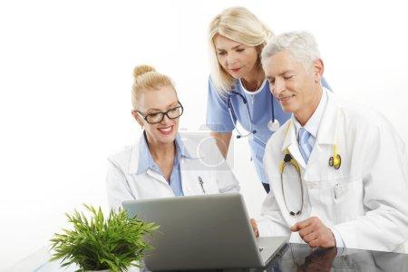 Photo pour Portrait d'un homme médecin consultant avec une femme médecin et infirmière. Groupe d'équipe médicale travaillant sur ordinateur portable. Isolé sur fond blanc . - image libre de droit