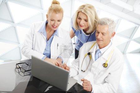 Photo pour Portrait d'un homme médecin consultant avec une femme médecin et infirmière. Groupe d'équipe médicale travaillant sur ordinateur portable à l'hôpital . - image libre de droit