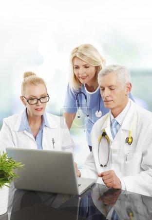 Photo pour Portrait d'un homme médecin consultant avec une femme médecin et infirmière. Groupe d'équipe médicale travaillant sur ordinateur portable . - image libre de droit