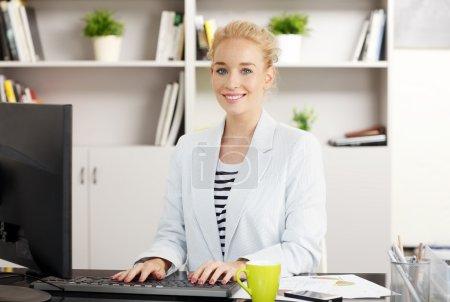 Photo pour Portrait de jeune assistant travaillant au bureau devant l'ordinateur tout en regardant la caméra et en souriant. Femme de vente souriante tapant sur le clavier . - image libre de droit
