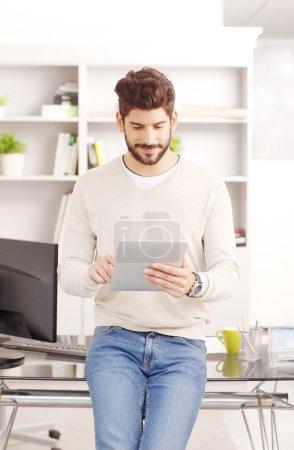 Photo pour Portrait de jeune vendeur debout au bureau devant le bureau et tenant dans sa main une tablette numérique. Homme d'affaires touchant l'écran tout en écrivant un e-mail sur le pavé tactile . - image libre de droit