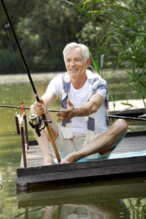 Senior man  at the lakeside and fishing.