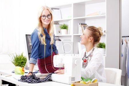 Foto de Retrato de jóvenes empresarias que trabajan juntas en un nuevo proyecto mientras están sentadas en el estudio de diseño frente a la máquina de coser y la computadora. Creativos sonrientes consultando sobre moda. Pequeñas empresas . - Imagen libre de derechos