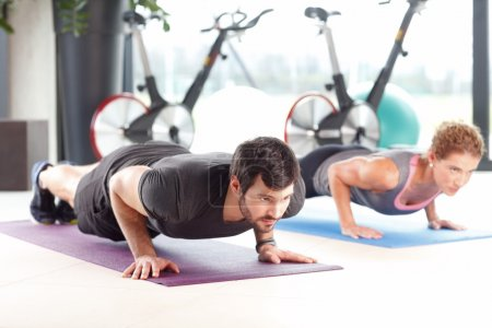 Woman and man doing push ups at the gym.