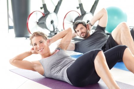 Photo pour Portrait d'un homme et une femme entraîner ensemble au gymnase. Entraîneur personnel, faire des redressements assis dans la salle de remise en forme. - image libre de droit