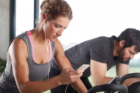 Photo pour Close-up portrait of gym members participating in a spinning class while training together at fitness center. Sporty woman listening music at her mobile phone. - image libre de droit
