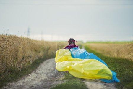 Photo pour Fille avec drapeau ukrainien près d'un champ de blé - image libre de droit