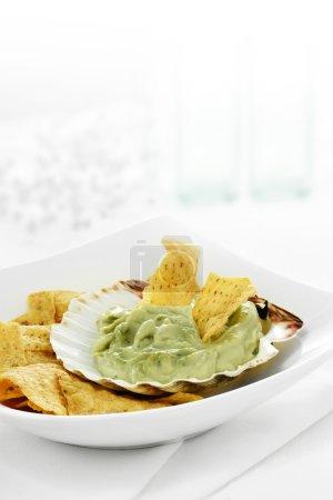 Photo pour Guacamole et trempage de copeaux de tortilla sur un fond blanc brillant avec espace de copie . - image libre de droit