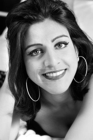 Photo pour Portrait d'une femme indienne jeune, souriante, incroyablement belle, heureuse et confiante à la recherche directement à la caméra tout en vous relaxant sur son lit. - image libre de droit