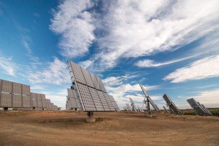 Foto de Vista de un campo de paneles solares fotovoltaicos que recogen energía en el campo con cielo azul y nubes blancas en el fondo - Imagen libre de derechos