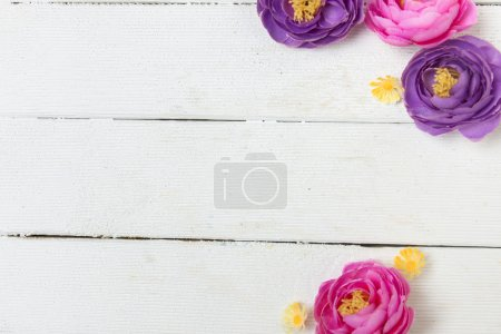 Fake pink and purple flowers isolated on a white background.