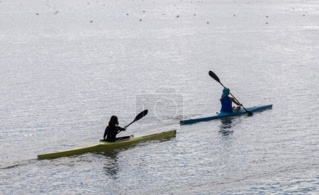 Two people kayak on the calm water