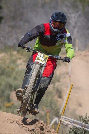 Foto de Competencia de Downhill, Biker salta rápidamente en el campo. - Imagen libre de derechos