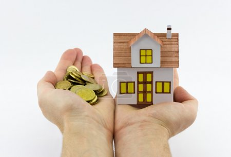 Photo pour Concept d'hypothèque. Vue rapprochée de l'homme tenant une petite maison de jouets dans une main et des pièces d'or dans l'autre main sur fond blanc - image libre de droit
