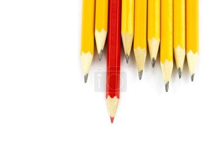 Photo pour Un crayon rouge se détachant de la rangée de crayons jaunes isolés sur fond blanc - image libre de droit