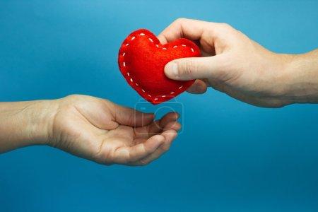 Hand legt das Herz in die Hand der Frau