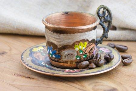 Photo pour Ancienne tasse en cuivre traditionnelle vintage avec grains de café torréfiés et sac sur table en bois - image libre de droit