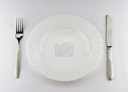 Photo for Close-up cutlery set - fork and knife on plate isolated on grey background - Royalty Free Image