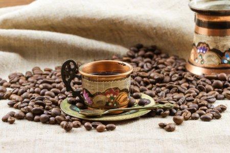 Photo pour Tasse traditionnelle en cuivre peint de café avec tas de grains de café torréfiés - image libre de droit