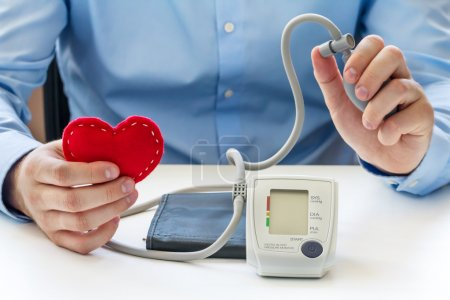 Doctor with digital blood pressure monitor