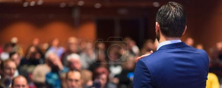 Foto de Vista trasera del altavoz dando una charla en la Conferencia de negocios corporativos. Audiencia en la sala de conferencias. Evento de negocios y Empresarismo. Composición panorámica. - Imagen libre de derechos
