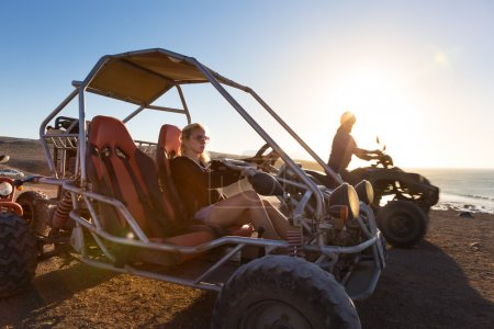 Woman driving quadbike in sunset.