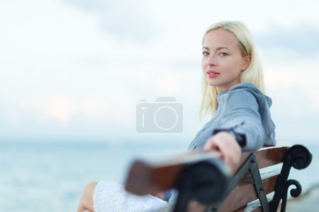 Lady sitting on a bench outdoors
