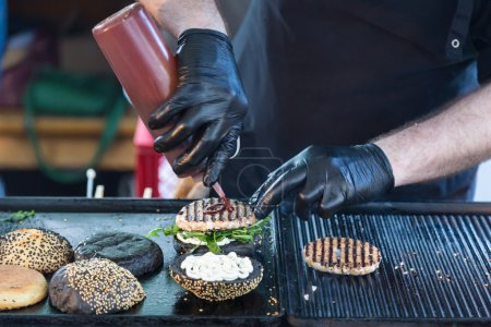 Photo for Chef making beef burgers outdoor on open kitchen international food festival event. Street food ready to serve on a food stall. - Royalty Free Image