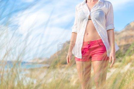 Foto de Relajado mujer en camisa blanca liberada disfrutando de la naturaleza hermoso paisaje sereno en la playa de Balos, Grecia. Concepto de vacaciones, libertad, felicidad, alegría y bienestar. - Imagen libre de derechos