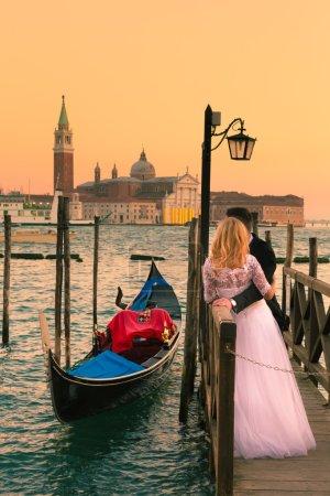 Photo pour Couple marié romantique dans la ville italienne romantique de Venise au coucher du soleil. Gondole traditionnelle vénitienne en bois et église catholique romaine de San Giorgio Maggiore en arrière-plan . - image libre de droit