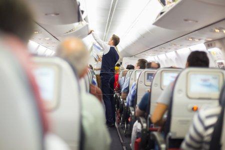 Photo pour Intérieur de l'avion avec des passagers sur les sièges et steward en uniforme fermeture coffre supérieur à. - image libre de droit
