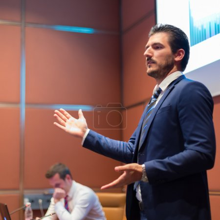Speaker giving talk at Business Conference.