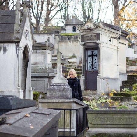 Photo pour Solitaire femme deuil par Pierre tombale, se souvenant des parents décédés dans le pere lachaise à paris, france. - image libre de droit