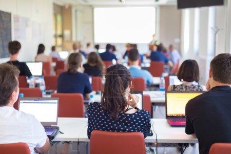 Photo pour Atelier à l'université. Vue arrière des étudiants assis et à l'écoute dans la salle de conférence faisant des tâches pratiques sur leurs ordinateurs portables . - image libre de droit