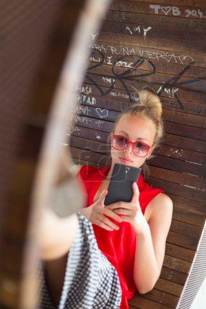 Young cheerful woman using smarthphone.